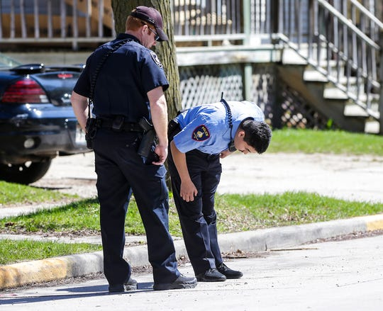 Fond du Lac Police officers Shawn Provot and Luis Diaz look at a bullet casing that was found Friday, April 26, 2019 in the 100 block of east Second Street in Fond du Lac, Wis. Doug Raflik/USA TODAY NETWORK-Wisconsin