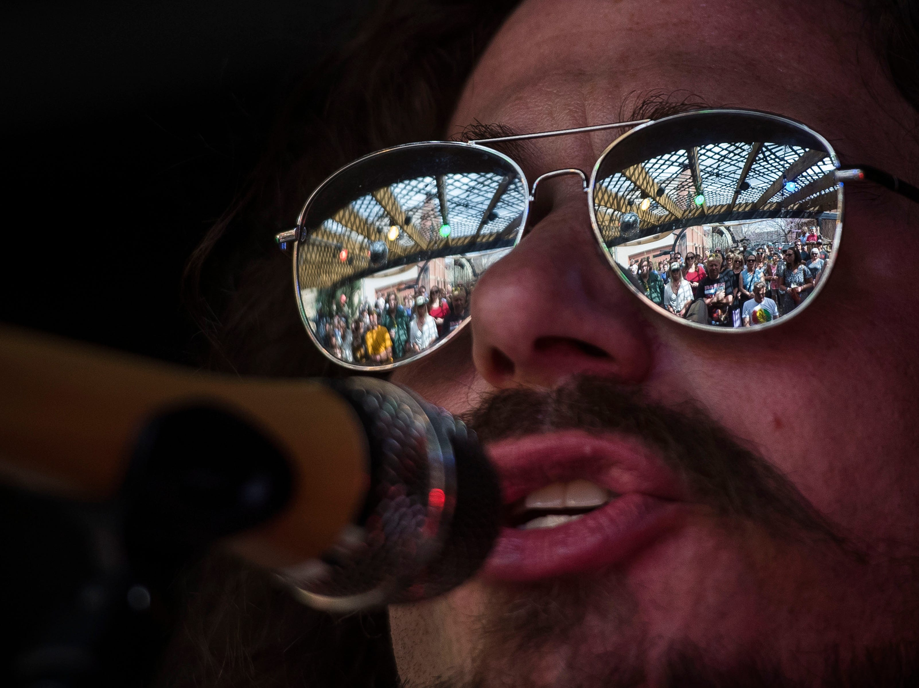 The crowd is reflected in Michael Kirkpartick's sunglasses as he performs at the Equinox Brewing back patio during the FoCoMX XI music festival on Friday, April 26, 2019, in Fort Collins, Colo.