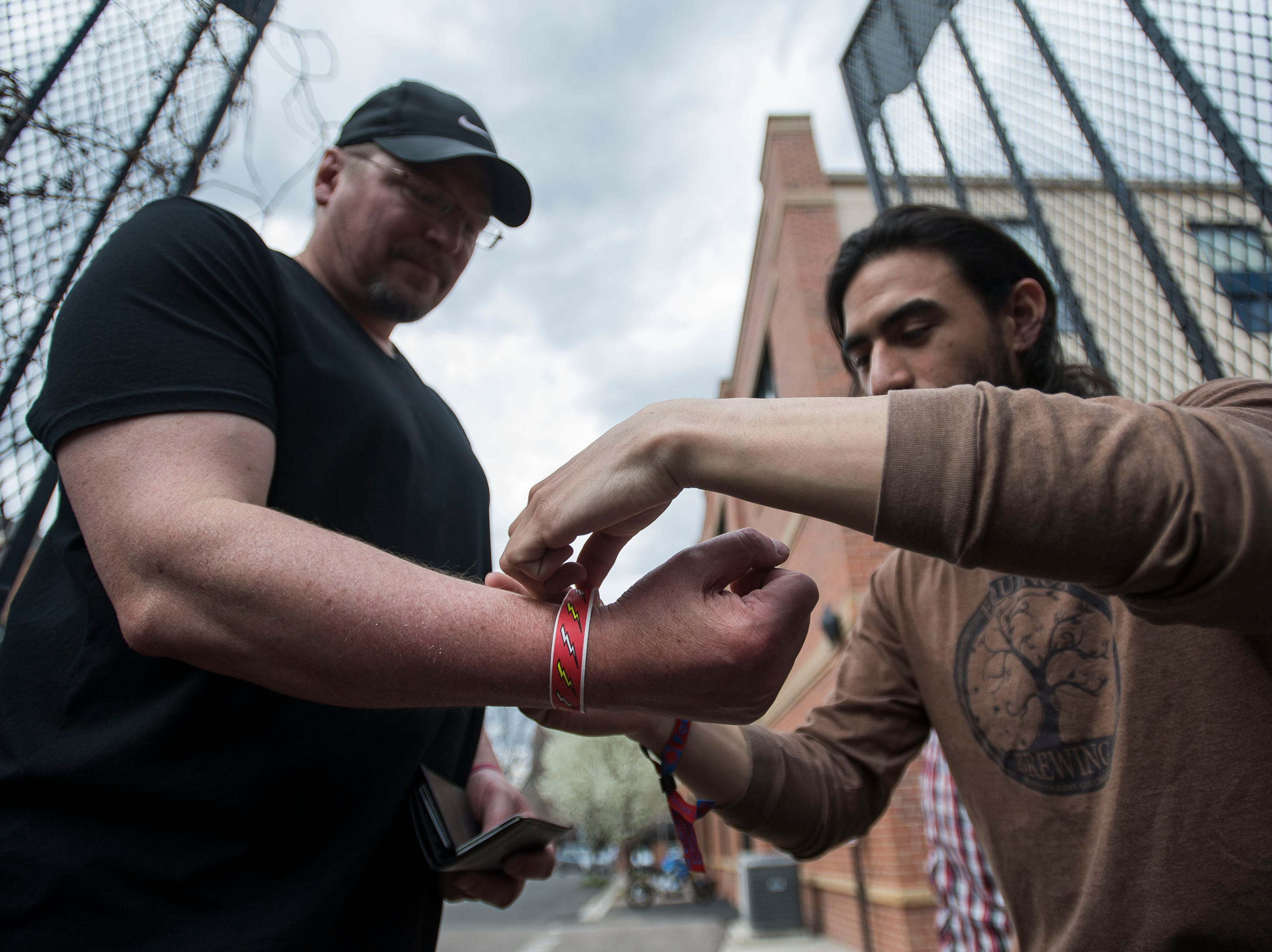 Mark Weber has a wristband stripped on by Equinox Brewing bartender Dennis Palacio before watching Michael Kirkpartick perform on the back patio during the FoCoMX XI music festival on Friday, April 26, 2019, in Fort Collins, Colo.