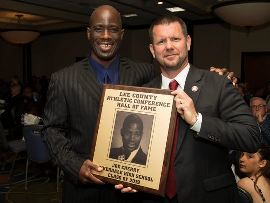 Joe Cherry, left, a 1998 Riverdale High School graduate, is inducted into the Lee County Athletic Conference Hall of Fame on Thursday in Fort Myers. Cherry played basketball at Riverdale. Riverdale High School principal Scott Cook, right, is among Cherry's supporters.