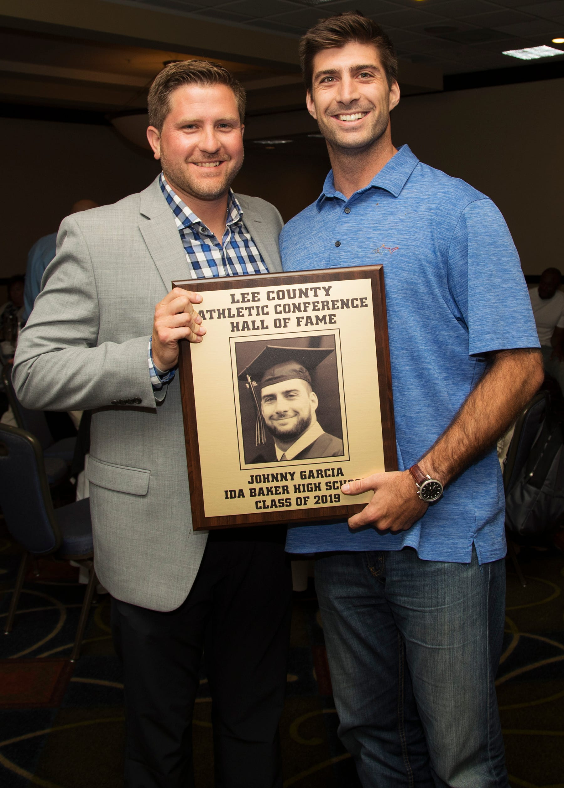 Jonathan Garcia, right, a 2010 Ida Baker High School graduate, is inducted into the Lee County Athletic Conference Hall of Fame on Thursday in Fort Myers. Garcia played football at Baker. Former Ida Baker football coach Brian Conn, left, is among Garcia's supporters.
