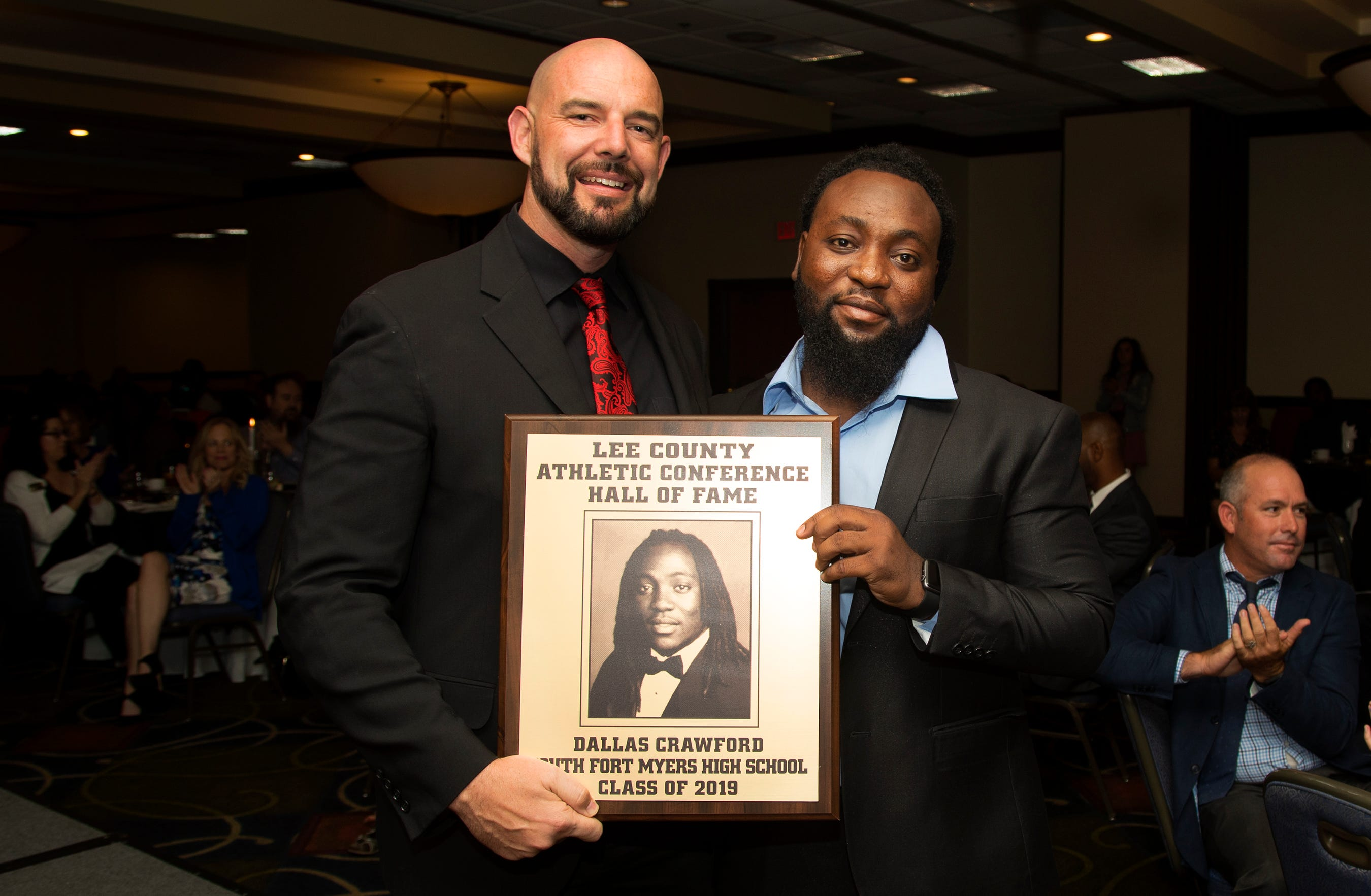Dallas Crawford, a 2011 South Fort Myers High School graduate, is inducted into the Lee County Athletic Conference Hall of Fame on Thursday in Fort Myers. Crawford played football at South. South Fort Myers High School principal Ed Mathews, left, is among Crawford's supporters.
