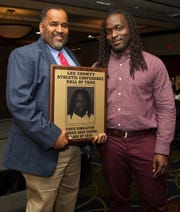 Chris Singleton, right, a 2005 Dunbar High School graduate, is inducted into the Lee County Athletic Conference Hall of Fame on Thursday in Fort Myers. Singleton played football at Dunbar. Singleton honored Dunbar High School principal Carl Burnside, left, in his acceptance speech.