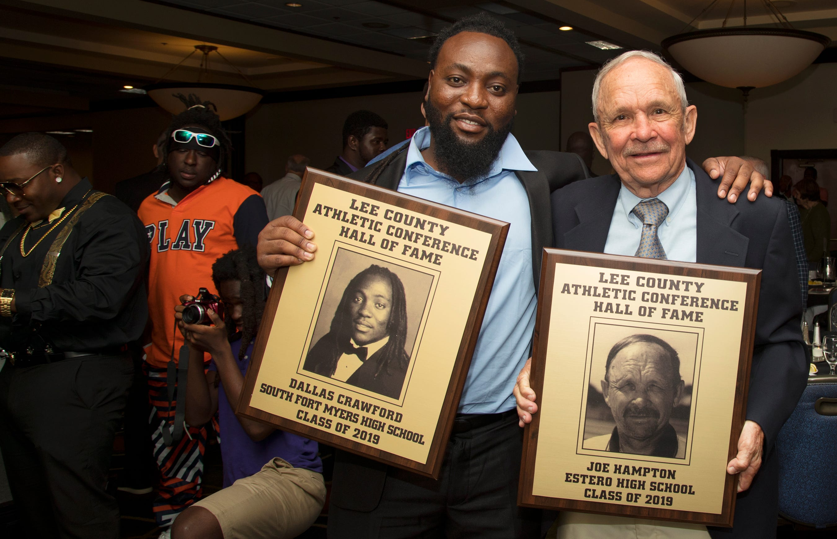 Dallas Crawford, left, a 2011 South Fort Myers High School graduate, and Joe Hampton, a former football coach at Estero High School, are inducted into the Lee County Athletic Conference Hall of Fame on Thursday in Fort Myers. Crawford played football at South.
