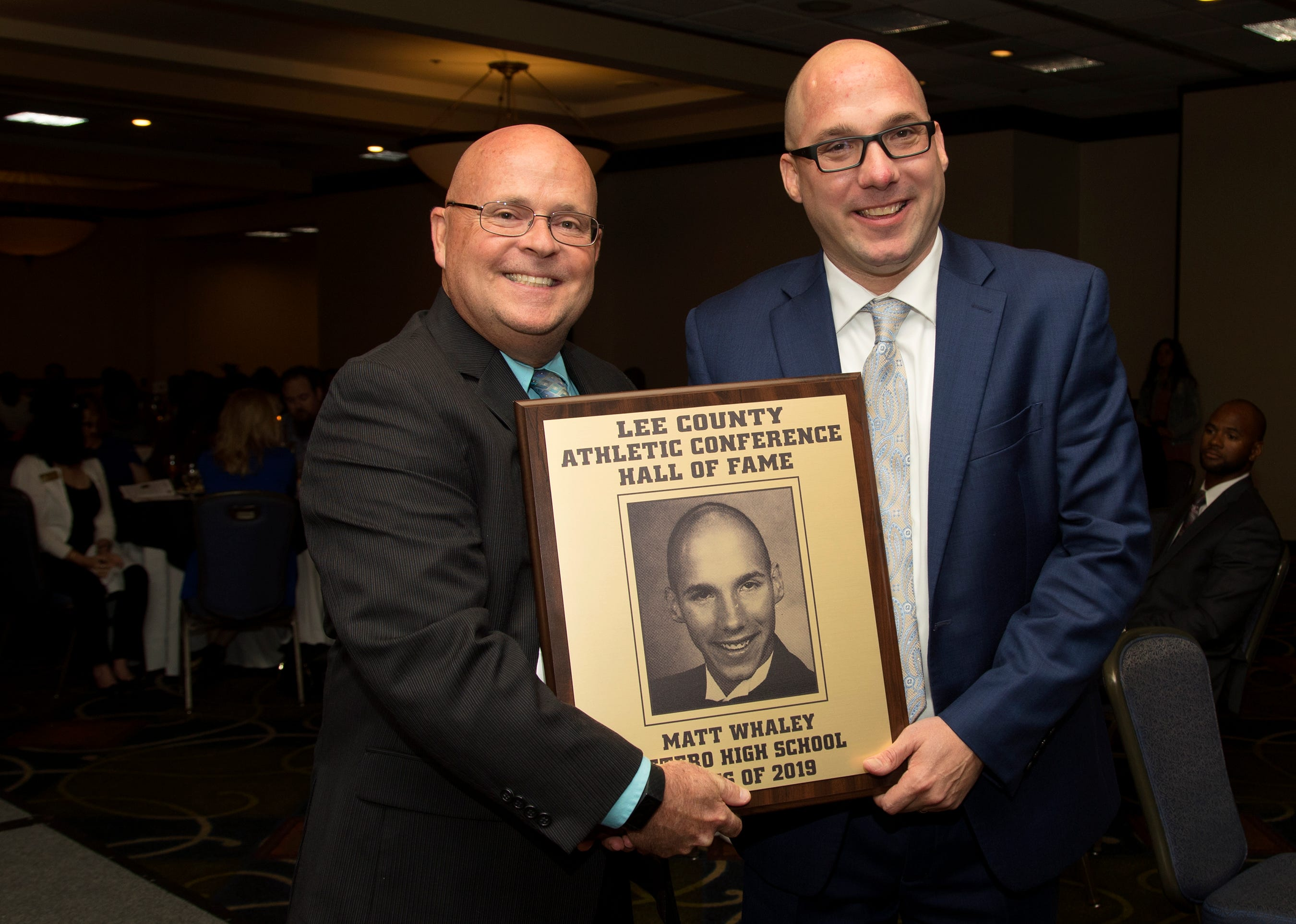 Matt Whaley, right, a 1996 Estero High School graduate, is inducted into the Lee County Athletic Conference Hall of Fame on Thursday in Fort Myers. Whaley ran track and cross country at Estero. Estero High School principal Clayton Simmons, left, is among Whaley's supporters.