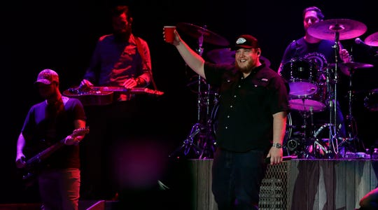 Luke Combs raises a glass to the crowd to kick off his 90-minute show Thursday at the Resch Center in Ashwaubenon. The 29-year-old singer/songwriter showed up for the encore in a Brett Favre Packers jersey.