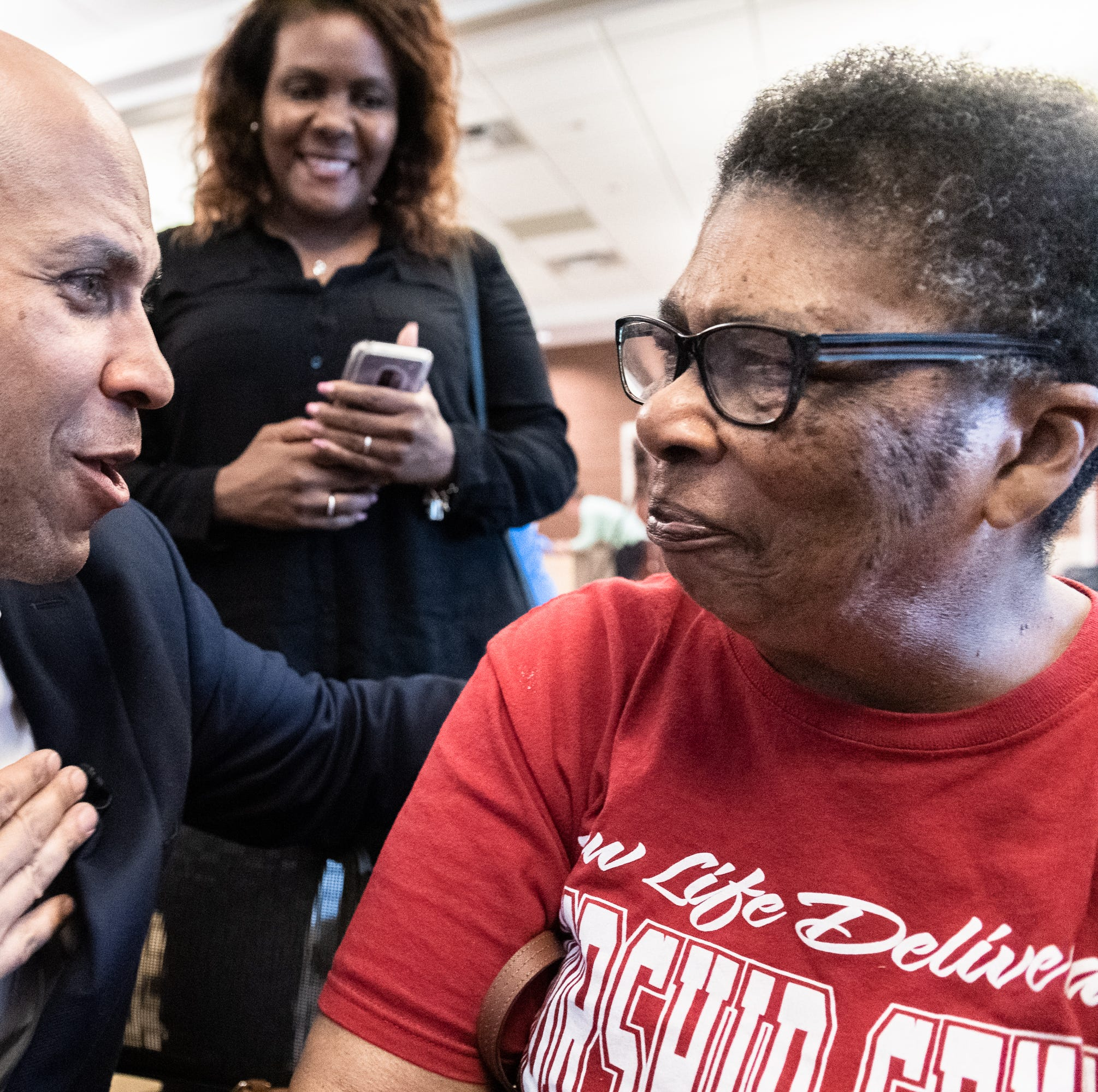 """Cory Booker, U.S senator from New Jersey, and a 2020 democratic presidential candidate thanks Shirley Gray, 78, of Spartanburg, after she presented him with a giclee print made by her late husband, Johnnie Lee Gray titled """"A Cloud of Witnesses"""" which depicts the ancestors who fought for civil rights at Senator Booker's rally at the C.C Woodson Community Center in Spartanburg during his visit to the city Thursday, Apr. 25, 2019."""