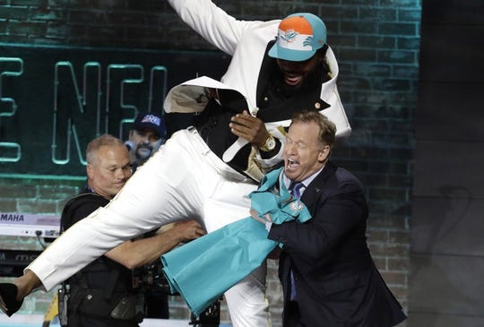 Christian Wilkins attempts a chest bump with NFL Commissioner Roger Goodell Thursday night in Nashville, Tenn.