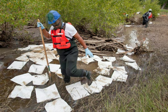 FILE - This July 11, 2011, file photo, shows an oil spill crew worker for Oil Mop Emergency Response stepping out of a ring of absorbent pads along a flood plain of the Yellowstone River where oil was found collected, near Laurel, Mont. Exxon Mobil Corp. has agreed to pay a $1.05 million penalty to settle alleged federal water pollution violations resulting from a 2011 oil pipeline spill into Montana's Yellowstone River. (AP Photo/Julie Jacobson, File)
