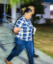 Marisha Ann Fegurgur Rabago is escorted from the Guam Police Department precinct in Hagåtña April 24.