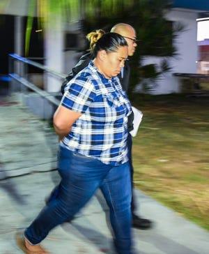 Marisha Ann Fegurgur Rabago is escorted from the Guam Police Department precinct in Hagåtña April 24.