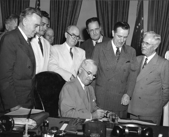President Harry S. Truman (seated) signs the Organic Guam Act of 1950. From left: Sen. Joseph C. O'Mahoney, Wyoming; Carlos Taitano, legislative representative of Guam; Harold Seidman, Bureau of the Budget; Secretary of the Navy Francis Matthews; Sen. Clinton P. Anderson, New Mexico; Secretary of the Interior Oscar Chapman; and Sen. Hugh Butler, Nebraska.