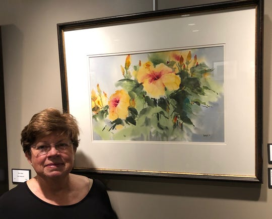 "Henderson's Marka Kroeger poses with her work, ""Spring Colors"""