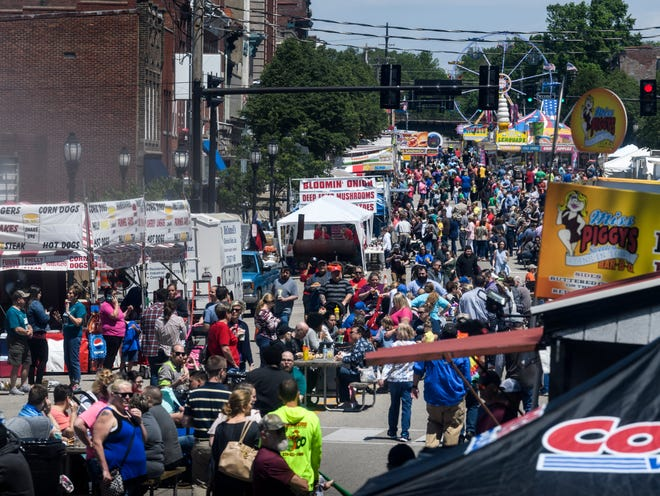 People walk along Main Street looking for a food booth to stop at during the lunchtime rush on the first day of the Henderson Breakfast Lions Club's 32nd annual Tri-Fest in downtown Henderson, Ky., Friday, April 26, 2019. Tri-Fest continues through Sunday, April 28, with over 50 food booths, 5k run and walk, carnival rides, live music and more.