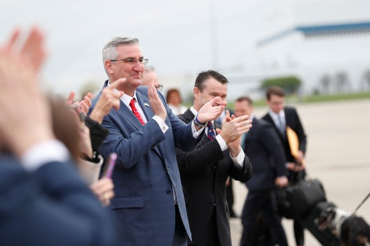 Gov. Eric Holcomb and Sen. Todd Young applaud Vice President Mike Pence as he gets off Air Force 2 after landing at the Indianapolis International Airport on April 26, 2019. Pence was in town to speak before the 2019 NRA Meeting and Exhibit at Lucas Oil Stadium.