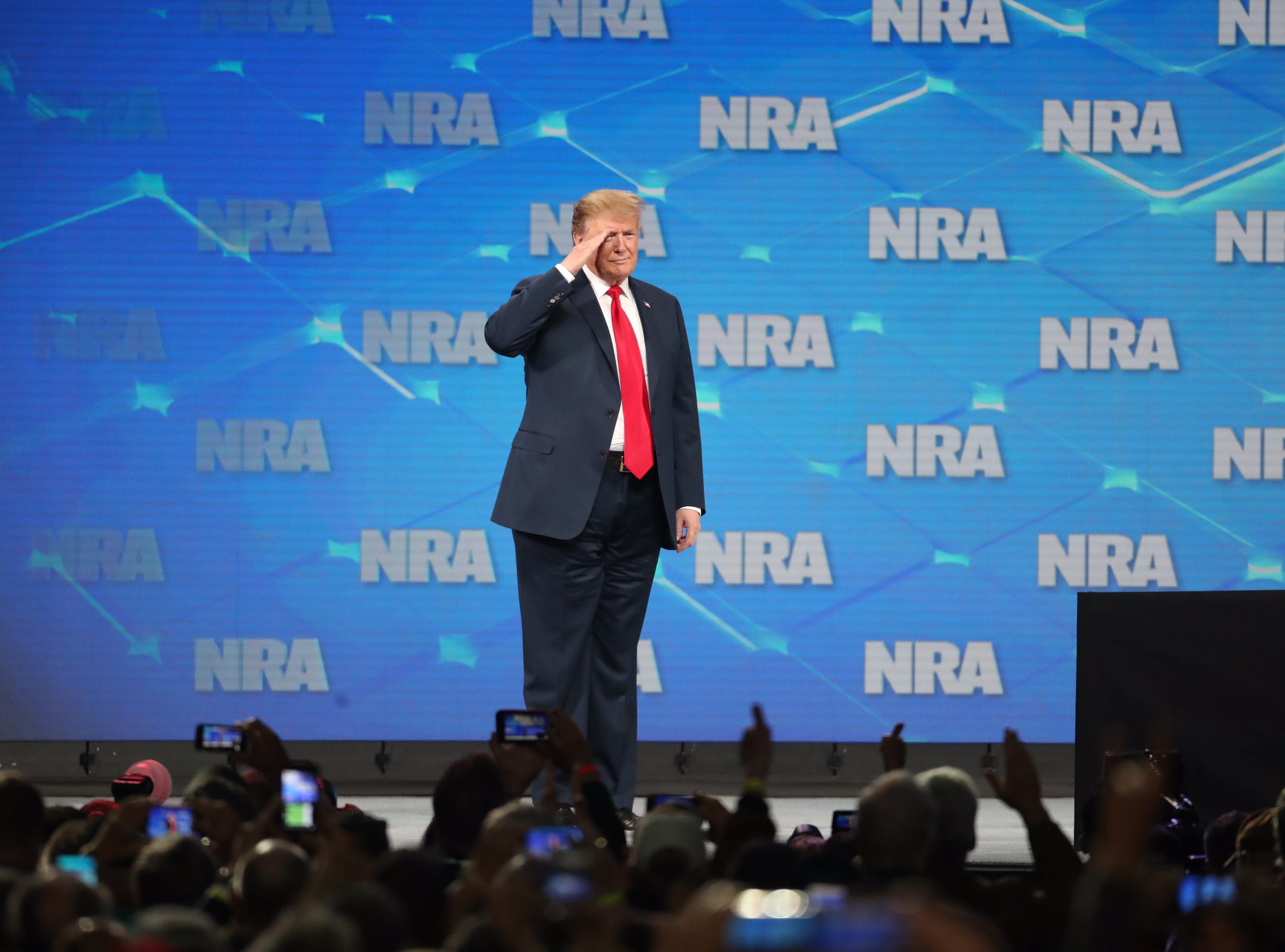 President Donald Trump salutes the crowd at the National Rifle Association Institute for Legislative Action Leadership Forum, Friday, April 26, 2019, at Lucas Oil Stadium in Indianapolis. The forum is part of the 148th NRA annual meetings and exhibits in Indianapolis.