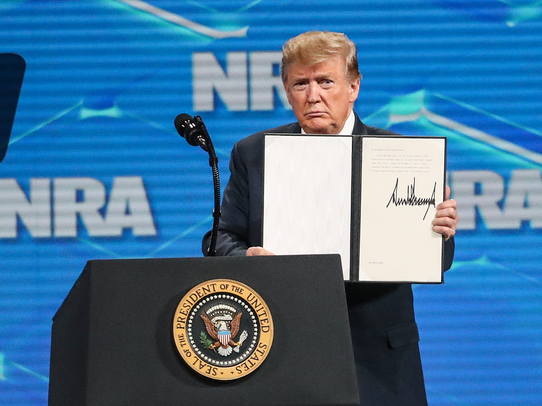 United States President Donald Trump holds up a letter to the Senate, after signing it in front of a crowd during the National Rifle Association Institute for Legislative Action Leadership Forum, Friday, April 26, 2019, at Lucas Oil Stadium in Indianapolis. The letter informed the Senate of his intent to remove the United States signature from the UN Arms Trade Treaty.