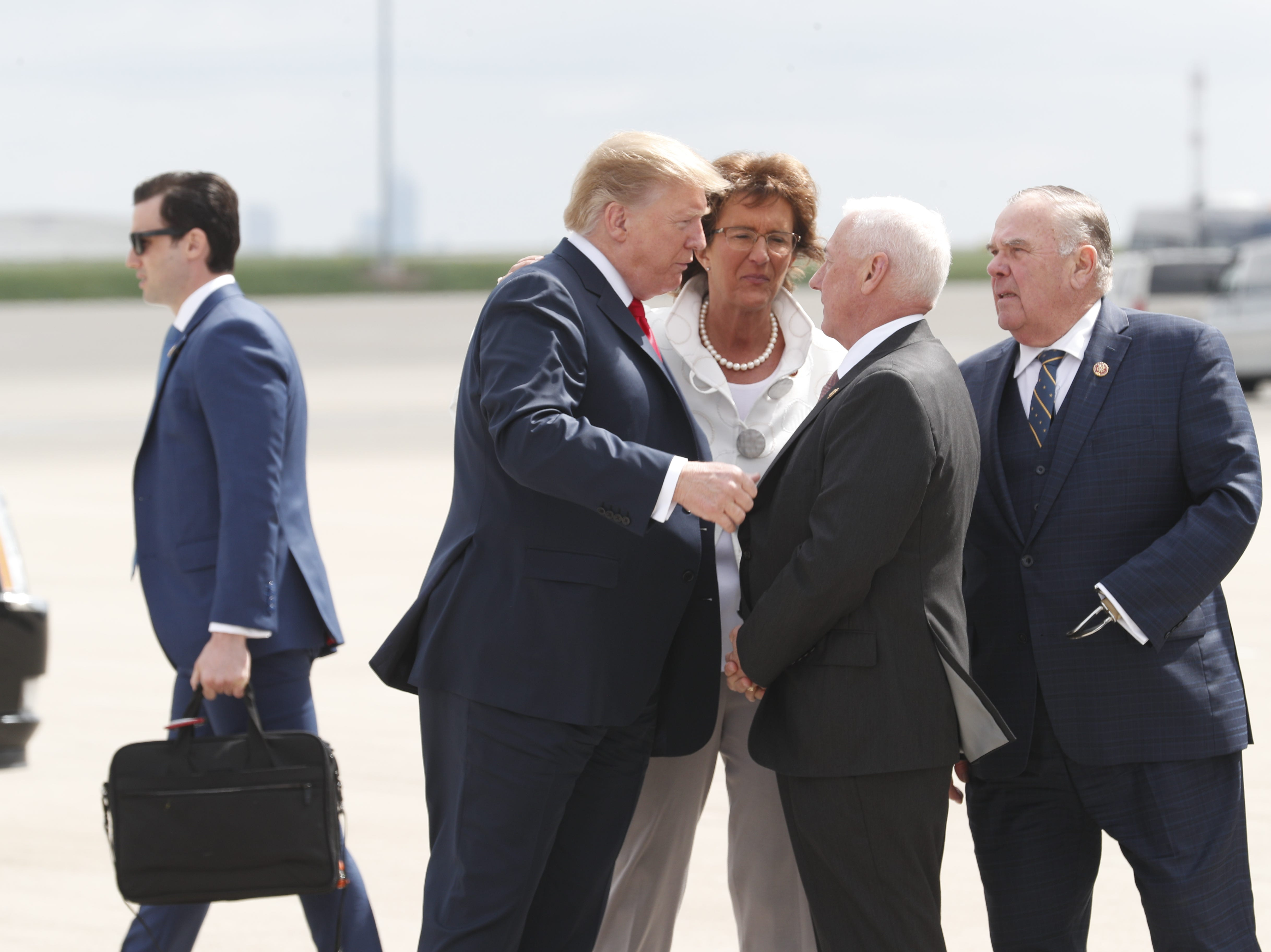 President Donald Trump talks with Congressman Greg Pence, brother of Vice President Mike Pence at the Indianapolis International Airport on Friday, April 26, 2019.  Congresswoman  Jackie Walorski and Congressman Jim Baird look on. Trump will speak at the NRA Institute for Legislative Action (NRA-ILA) Leadership Forum at Lucas Oil Stadium.