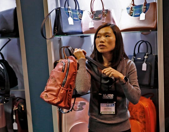 Julia Arnold shows a bullet-proof backpack sold at the Asfaleia booth at the 2019 NRA convention exhibits at the Indiana Convention Center, Friday, April 26, 2019.  They sell armor-plated bags for concealed carry of handguns.  They have purses, messenger bags, and backpacks with magnetic quick-access pockets, hidden holsters, and room for bullet-proof plates.