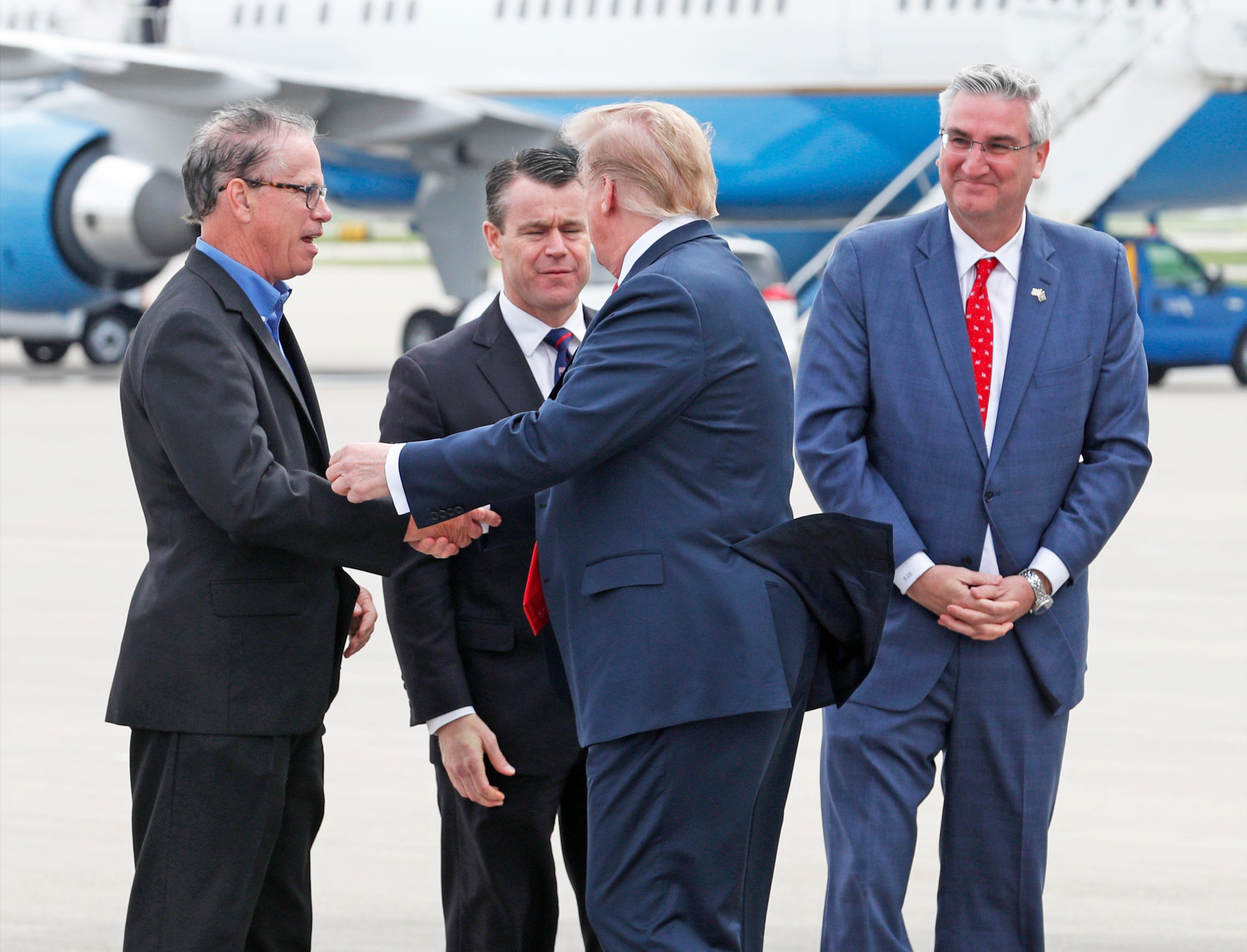 President Donald Trump shakes hands with Sen. Mike Braun as Sen. Todd Young and Gov. Eric Holcomb look on after the president arrived at the Indianapolis International Airport on Friday, April 26, 2019. Trump will speak at the NRA Institute for Legislative Action (NRA-ILA) Leadership Forum at Lucas Oil Stadium.