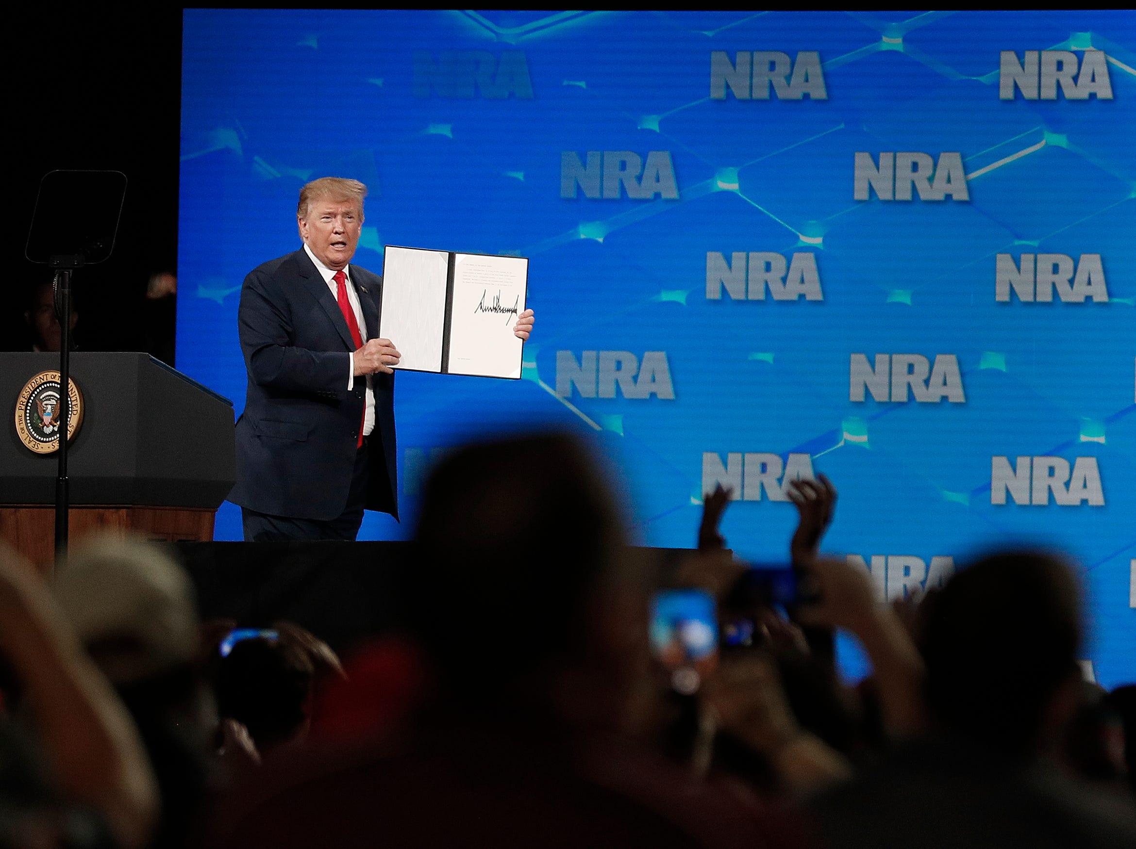 President Donald Trump shows the executive order he just signed to his supporters at the NRA-ILA Leadership Forum at Lucas Oil Stadium on Friday, April 26, 2019.