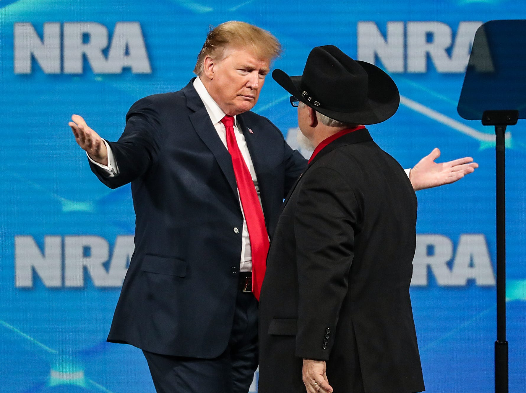 United States President Donald Trump hugs Stephen Willeford, who helped stop an active shooter at a baptist church in Sunderland Springs, Texas, during the National Rifle Association Institute for Legislative Action Leadership Forum, Friday, April 26, 2019, at Lucas Oil Stadium in Indianapolis.