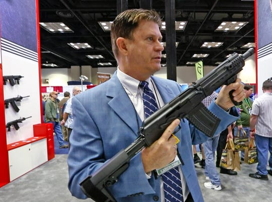 Jonathan Mossberg shows a Komrad, an American-made  rifle that fires shotgun ammunition, at the Kalashnikov USA booth during the 2019 NRA convention exhibits in the Indiana Convention Center, Friday, April 26, 2019.