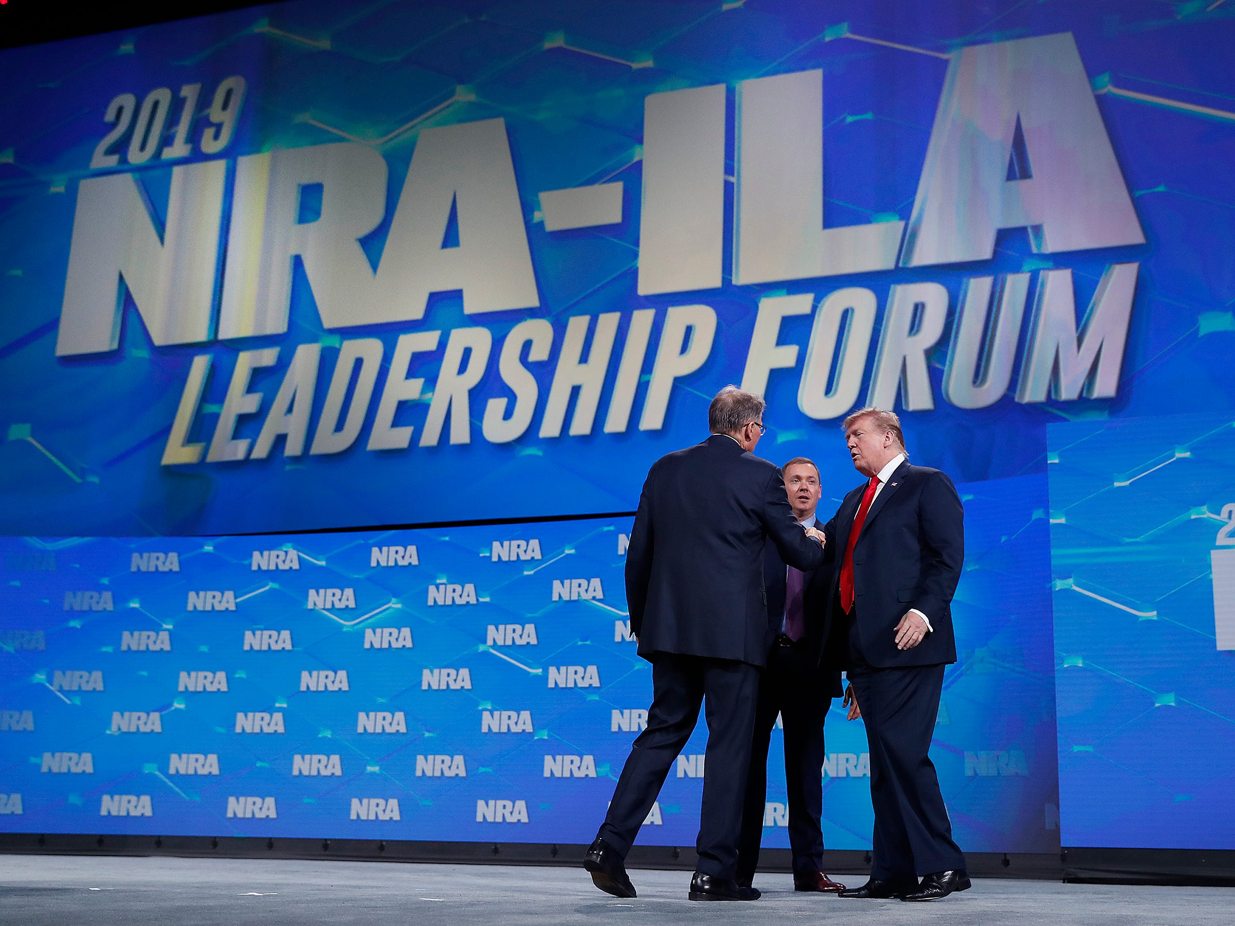President Donald Trump shakes hands with Chris Cox, Executive Director of the National Rifle Association's Institute for Legislative Action as Wayne LaPierre, Executive Vice President and Chief Executive Officer of the NRA looks on. President Trump addressed the National Rifle Association Institute for Legislative Action Leadership Forum, Friday, April 26, 2019, at Lucas Oil Stadium in Indianapolis. The forum is part of the 148th NRA annual meetings and exhibits in Indianapolis.