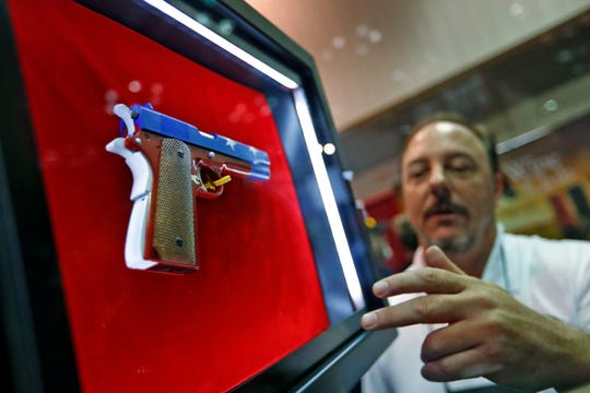 Sam Galler shows an InvictaSafe secure display case to display one's firearm like a work of art, at the 2019 NRA convention exhibits at the Indiana Convention Center, Friday, April 26, 2019.  The gun is held in place by magnets and surrounded by LED lights.  A hidden panel behind the display hides a place for magazines and ammunition.