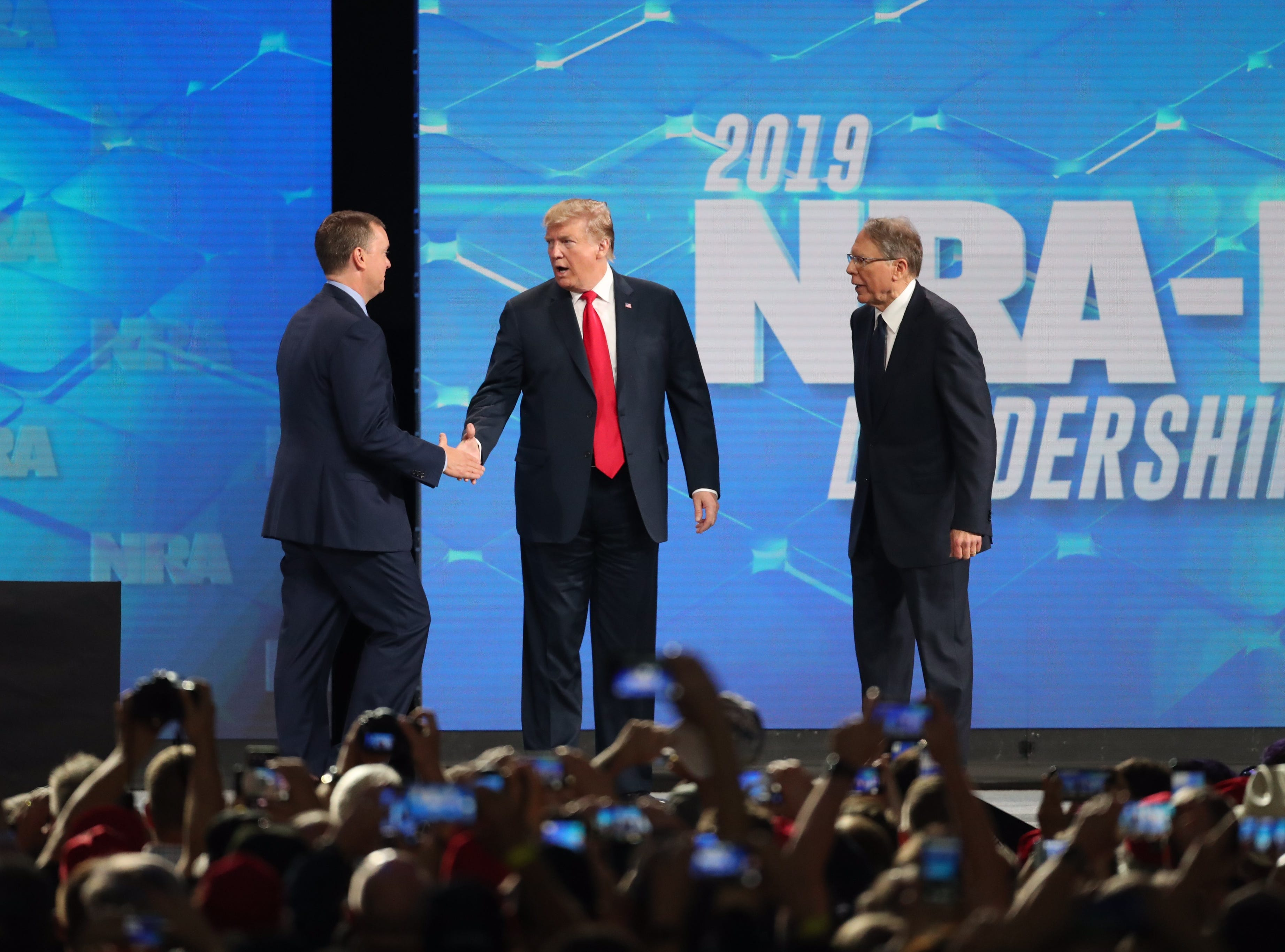 President Donald Trump shakes hands with Chris Cox, Executive Director of the National Rifle AssociationÕs Institute for Legislative Action as Wayne LaPierre, Executive Vice President and Chief Executive Officer of the NRA looks on. President Trump addressed the National Rifle Association Institute for Legislative Action Leadership Forum, Friday, April 26, 2019, at Lucas Oil Stadium in Indianapolis. The forum is part of the 148th NRA annual meetings and exhibits in Indianapolis.