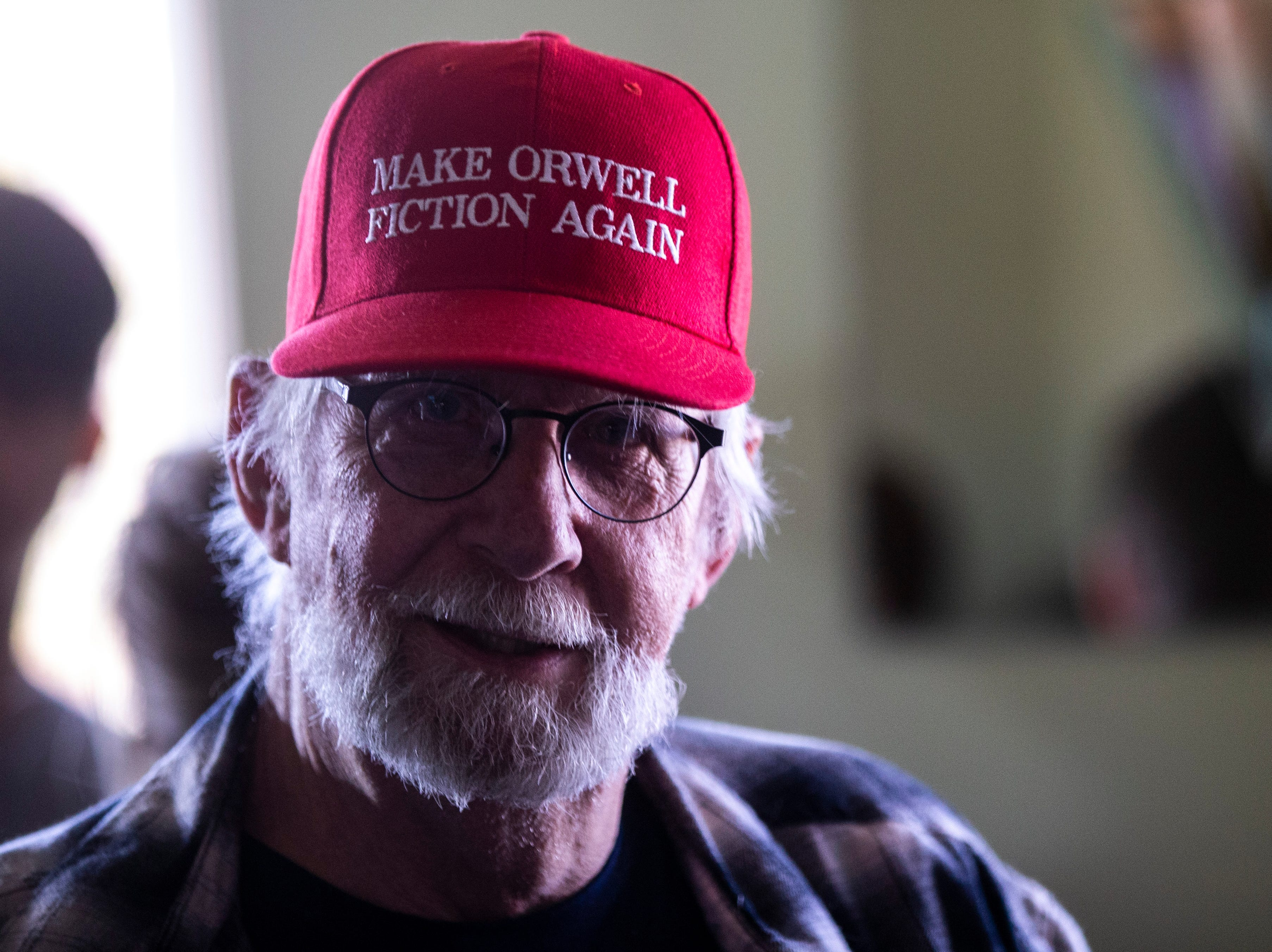 """Pieter Breitner, of Coralville, waits in line while wearing a red hat that reads, """"Make Orwell fiction again,"""" to take a photo with U.S. Sen. Elizabeth Warren, D-Mass., after a campaign event, Friday, April 26, 2019, at the Tipton Family Restaurant in Tipton, Iowa."""