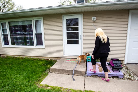 Tara Armstrong walks up to her front door with Walter Winston, her 3-year-old french bulldog, after a walk, Thursday, April 25, 2019, at her home in Iowa City, Iowa.