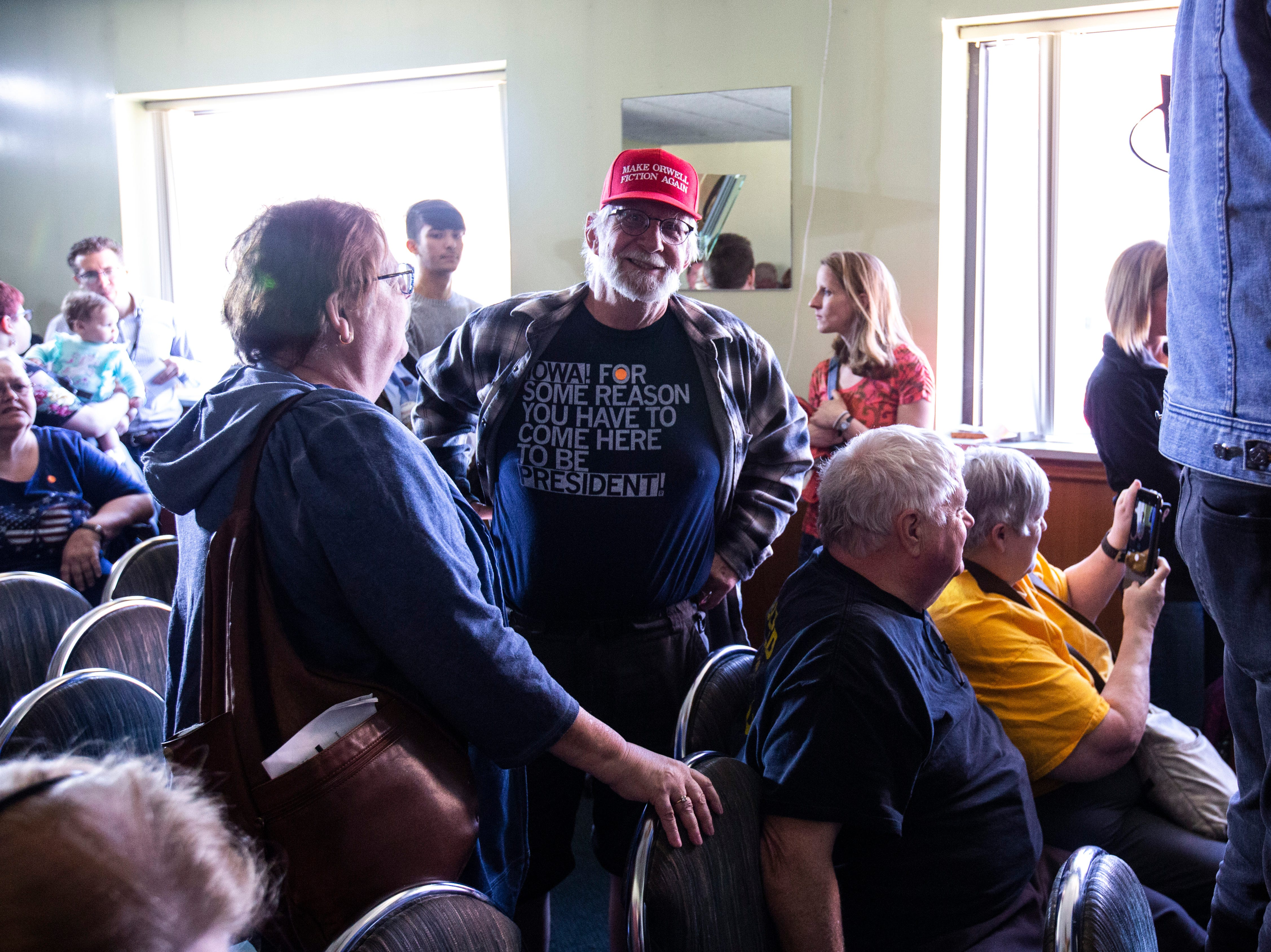 """Pieter Breitner, of Coralville, poses while wearing a red hat that reads, """"Make Orwell fiction again,"""" and a shirt designed by Ragyun that reads, """"Iowa! For some reason you have to come here to be president!"""" while waiting to take a photo with U.S. Sen. Elizabeth Warren, D-Mass., after a campaign event, Friday, April 26, 2019, at the Tipton Family Restaurant in Tipton, Iowa."""
