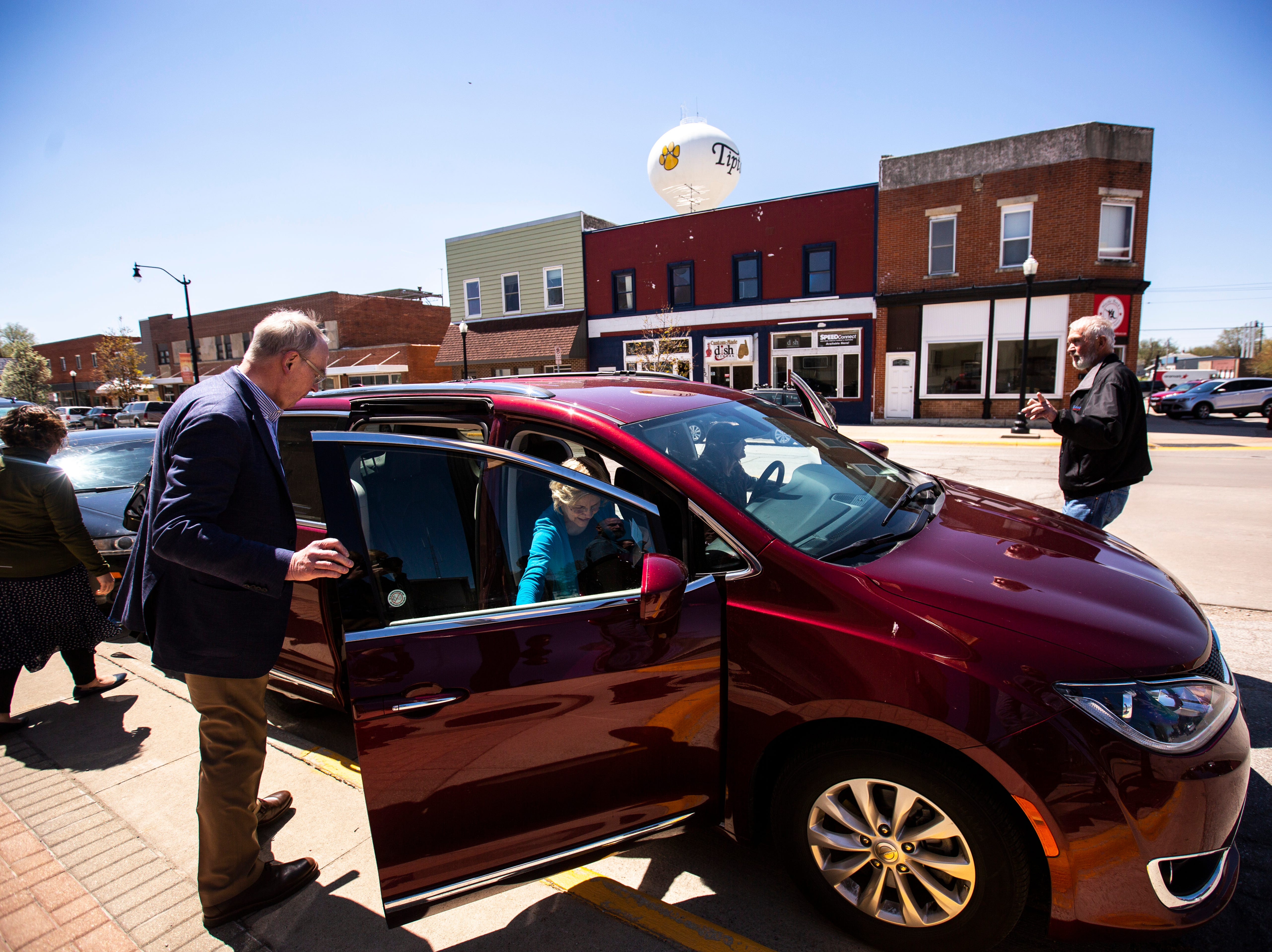 Bruce H. Mann, the husband of U.S. Sen. Elizabeth Warren, D-Mass., holds the door open for her to the passenger seat of a red Chrysler minivan after she spoke at a campaign event, Friday, April 26, 2019, at the Tipton Family Restaurant in Tipton, Iowa.