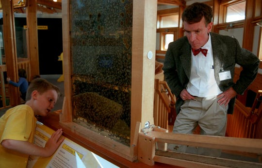 Bill Nye the Science Guy helps Sam O'Mara locate the queen bee in the bee exhibit at the Sciencenter in 2000. Nye, a Cornell University graduate, visited the museum to show his support for the expansion project as an honorary chairman for the capital campaign.