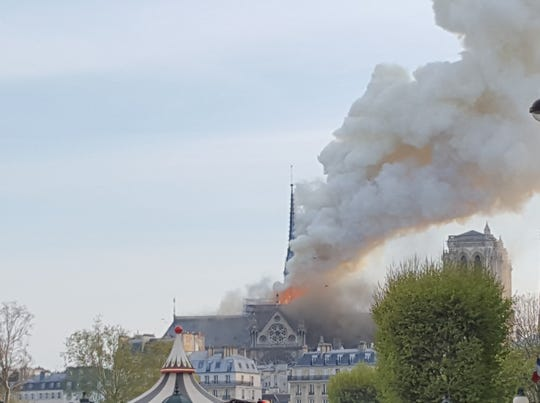 "UT Knoxville student Oliver Trigony spotted flames and smoke atop Notre Dame's roof after leaving a class in Paris on April 15. He snapped a few pictures ""to preserve what I witnessed,"" he said."