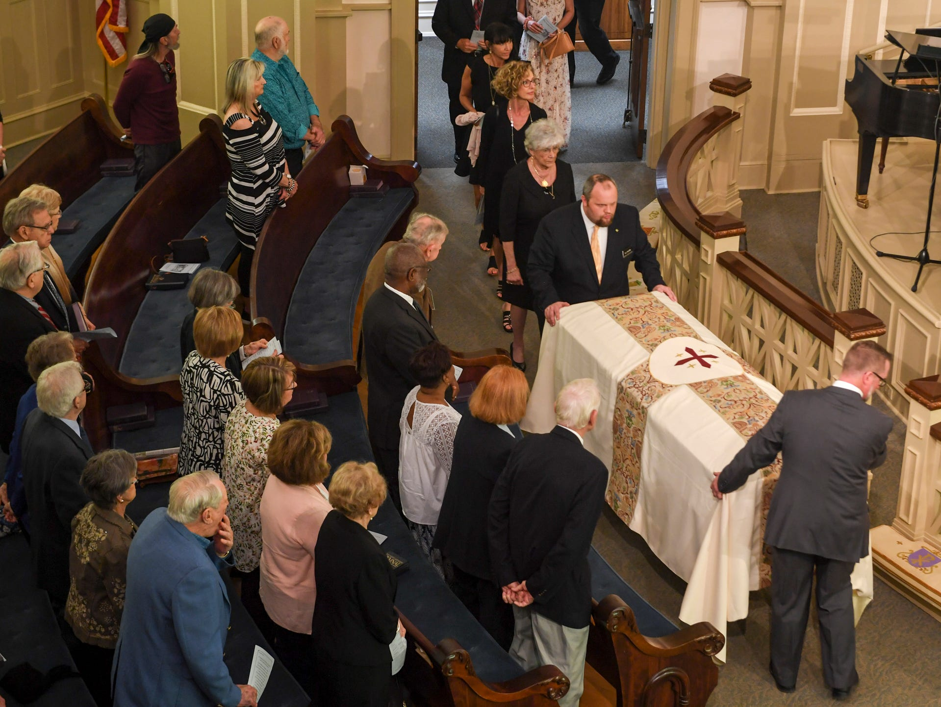 Funeral directors wheel Henry Harrison's casket into the sanctuary of First United Methodist Church during his Celebration of Life service, Friday, April 26, 2019.