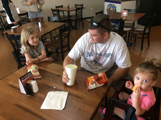 Marcus Wade and daughters Olivia (left, 4 years old) and Rylee (1) wait for their sandwich order.