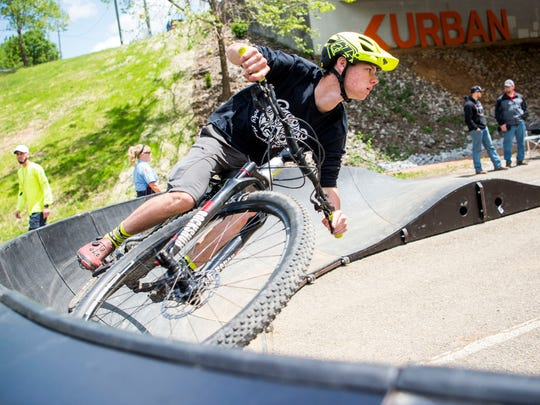 Hayden Connell rides his bike on a temporary bike track after Knoxville Mayor Madeline Rogero's final State of the City address held at the Urban Wilderness Gateway Park in South Knoxville on Friday, April 26, 2019.