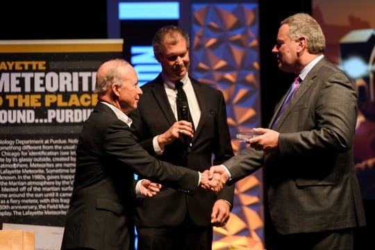 Ray DeThorn of the Field Museum in Chicago, right, delivers the Lafayette Meteorite to Purdue President Mitch Daniels, left, and West Lafayette Mayor John Dennis at Purdue's Loeb Playhouse on Thursday, April 25, 2019. The meteorite, once found in a drawer in a Purdue lab in 1929, is on loan from the Field Museum for Purdue's 150th anniversary, after students petitioned to get it back to campus. It will be on display in the lobby of the Neil Armstrong Hall of Engineering.