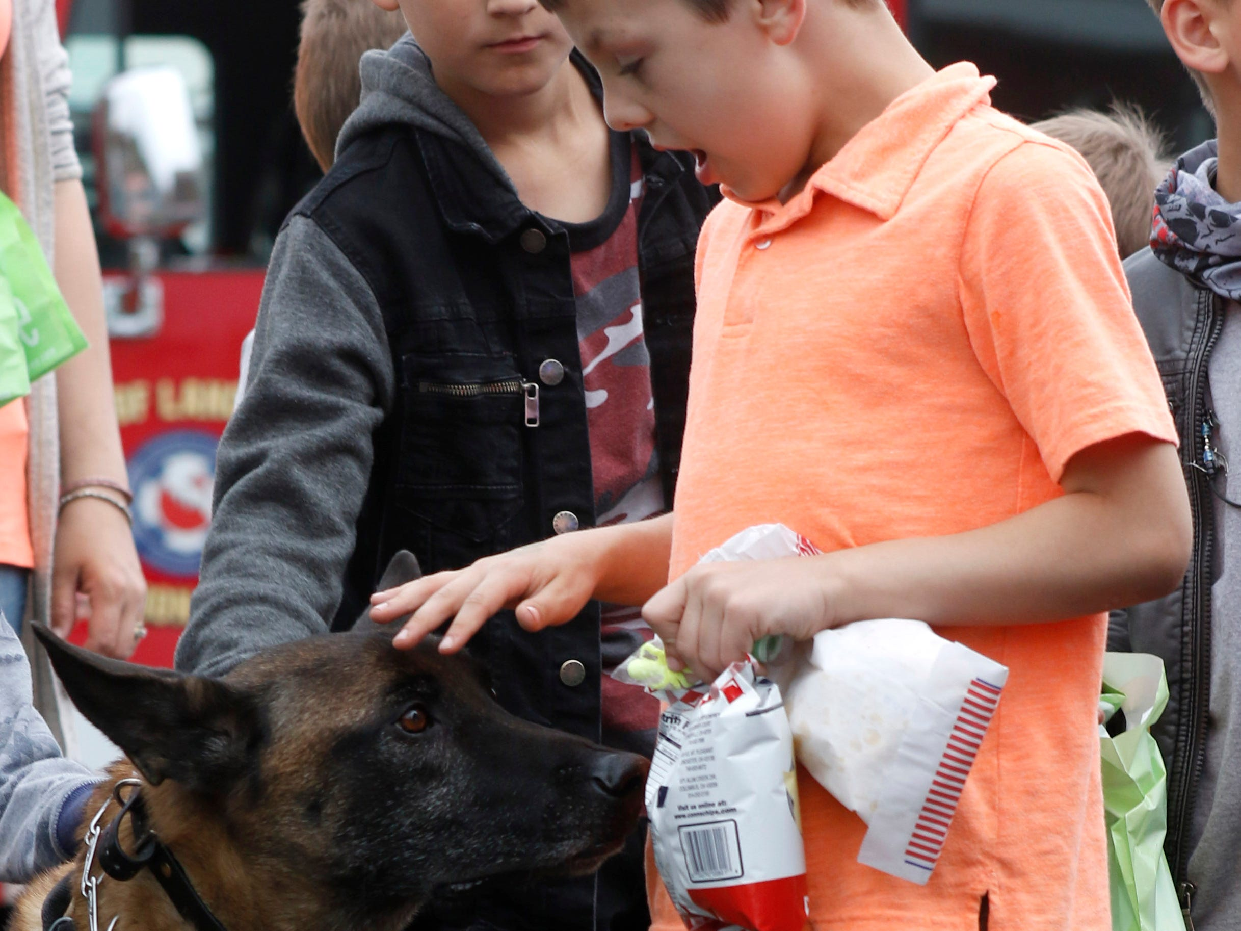 Carter Aneshansley, 7, pets Kahr a Fairfield County Sheriff's Office K-9 as Kahr tries to sniff out the popcorn and potato chips in Aneshansley's hand Thursday evening, April 25, 2019, at the Fairfield County Job and Family Services' annual Circus Night in downtown Lancaster.