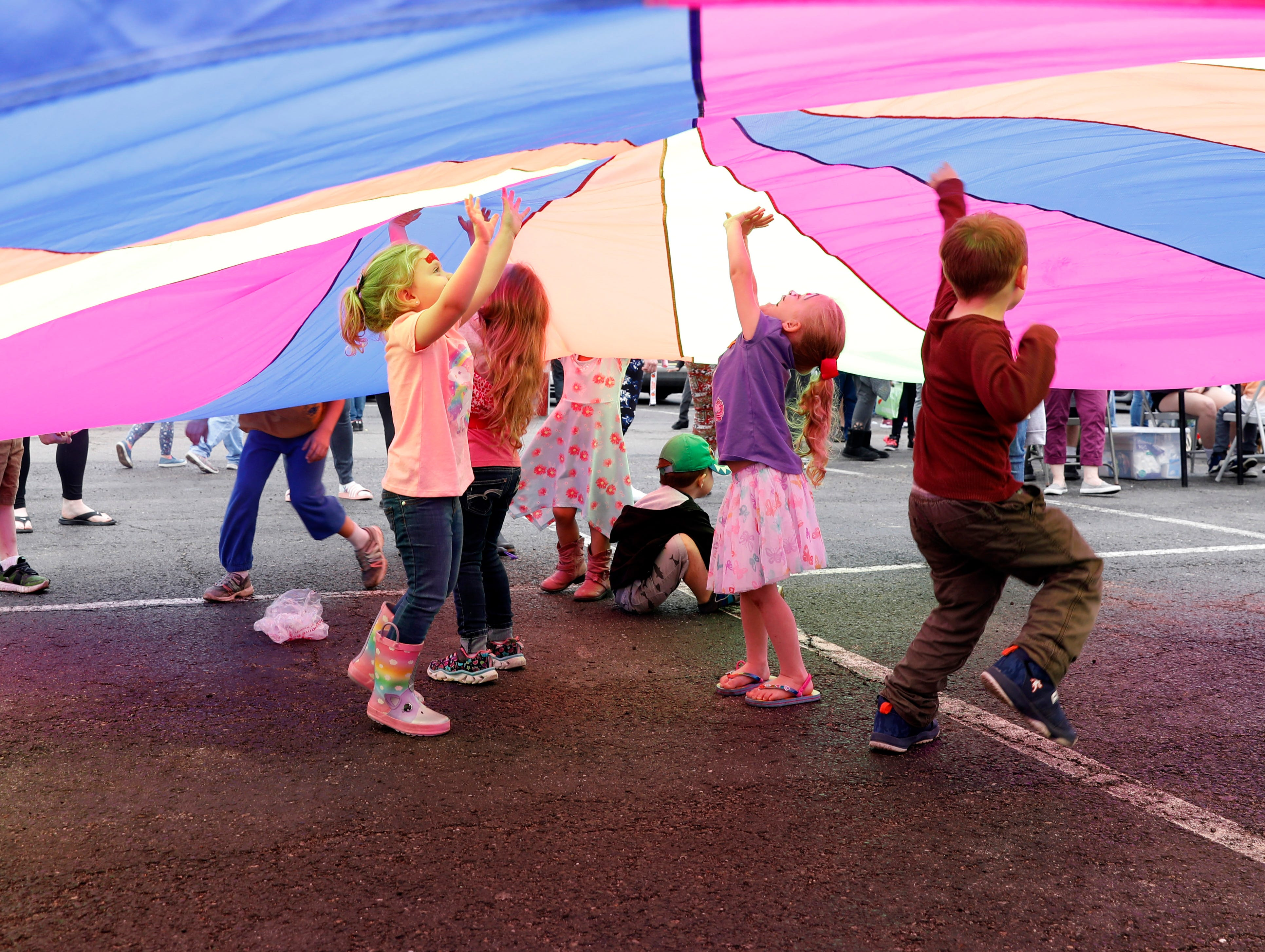 Children play under a parachute Thursday evening, April 25, 2019, during the Fairfield County Job and Family Services' annual Circus Night in downtown Lancaster.