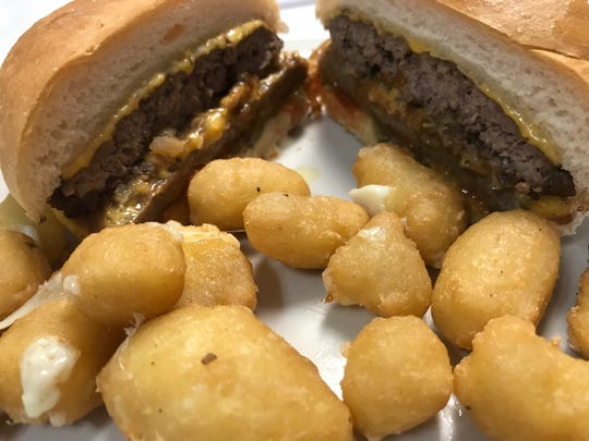 The Trivers Twin - a quarter-pound burger paired with a brat patty and smothered in cheese and fried onions - served with cheese curds.