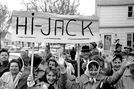 """This photo from John F. Kennedy's first visit to Milwaukee since becoming president is dated May 12, 1962. Two women hold up a """"Hi-Jack"""" sign as the presidential motorcade passes by."""