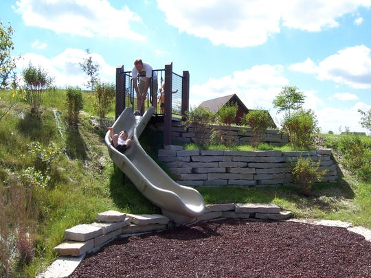 Fox River Park natural play area has a slide for younger kids built into an embankment.