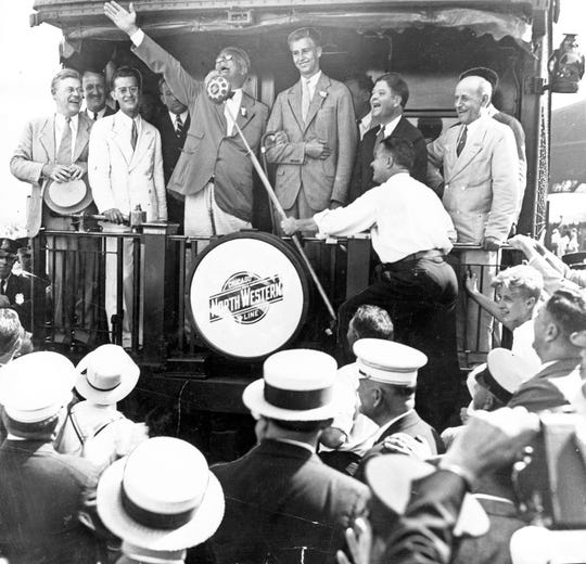 """In this photo dated Aug. 10, 1934,  President Franklin Delano Roosevelt speaks from the back of a railroad car. The original caption read, """"The thousands of Milwaukeeans who greeted President Roosevelt at the North Western depot Friday cherished the memory of his charming informality as revealed in these pictures. He is shown as he received the invitation of the Honey Creek C.C.C. camp to """"chow"""" and as he answered it. He has the whole platform laughing including (left to right) Senator Duffy, Congressman O'Malley; the president; his son, John; Senator La Follette and Gov. Schmedeman."""""""