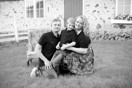 Becky Luedcke with her husband Mike and their son pose for a family photo. Becky has been professionally photographing families for over 18 years through her business, Forever Young Photography.