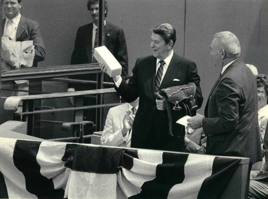 This photo of President Ronald Reagan's visit to Oshkosh is dated May 30, 1985. Reagan holds a block of cheddar cheese and Oshkosh B'Gosh bib overalls presented to him.