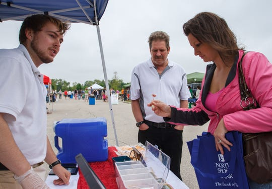 Ross Dahlke (left) offers up a taste of Harmony Specialty Dairy Foods cheese to Mike Benz and Ashley Feest at the Sussex Famers Market in 2015.