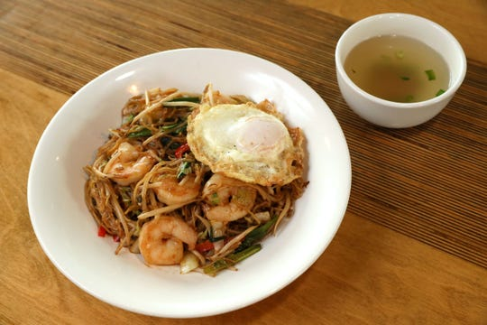 Yakisoba, a stir-fried dish of springy house ramen noodles, can be made with shrimp. It's topped with a fried egg and served with dashi broth on the side.